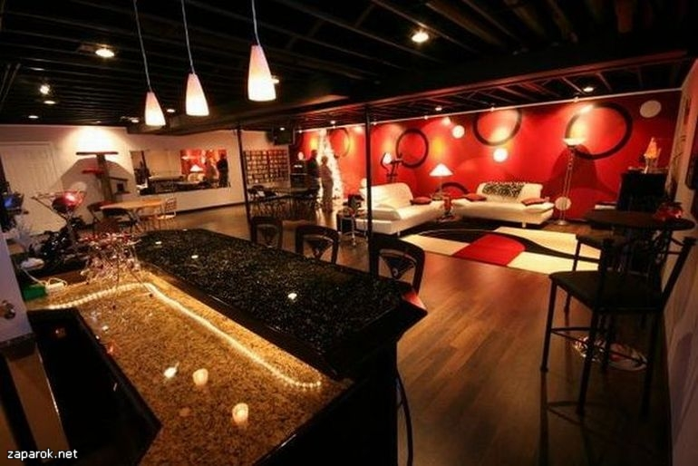 Comfortable man cave with Red color theme in Neil Kelly story on man caves.