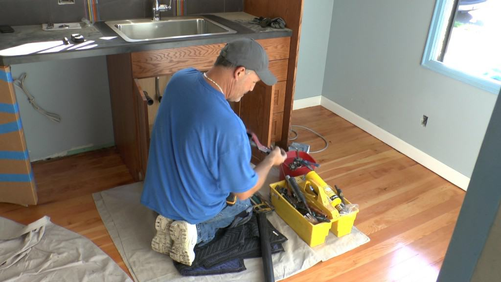 A Neil Kelly handyman repairs a sink