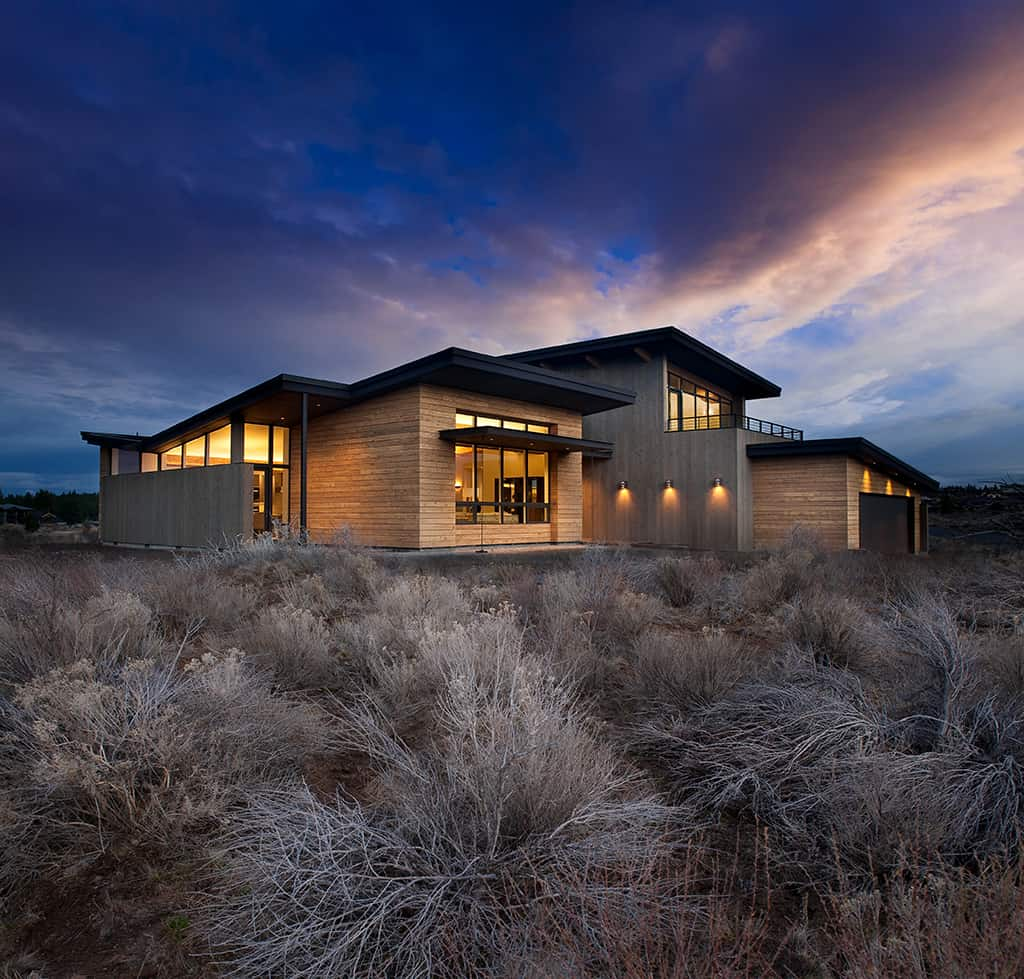 Mid-Century Tetherow Resort custom home at dusk with rustic landscaping