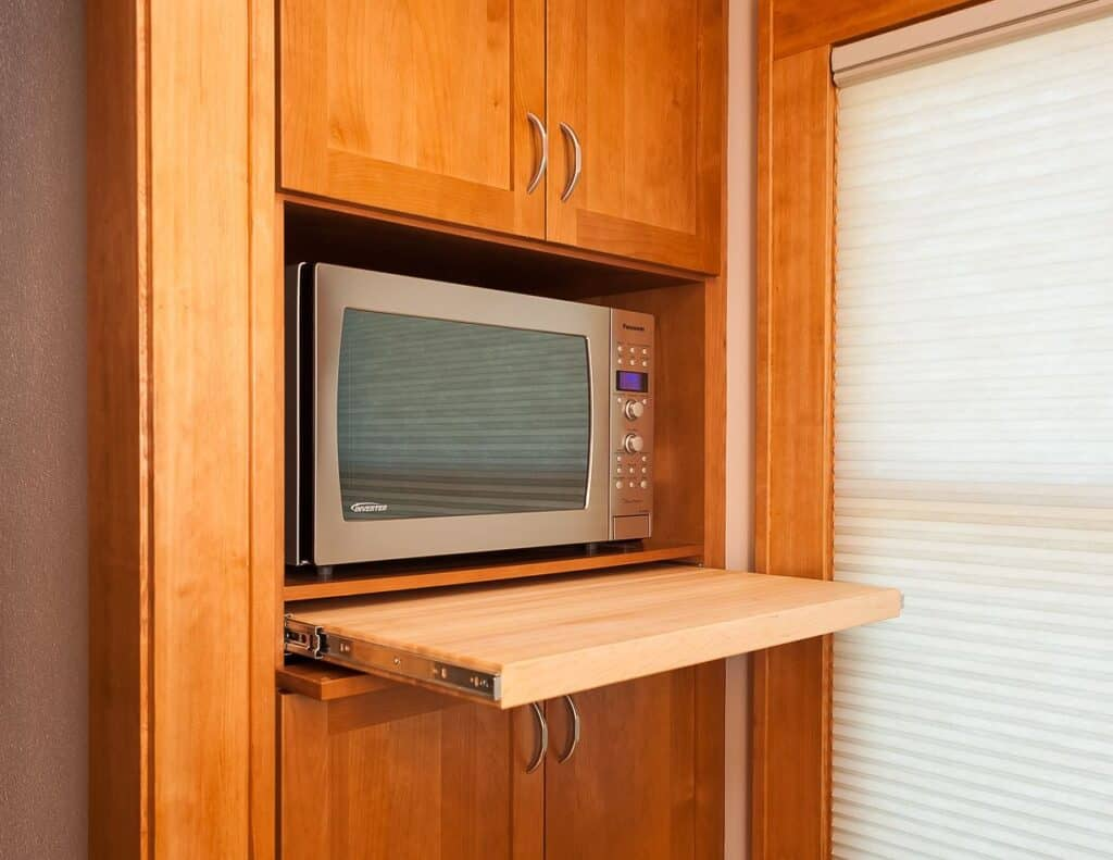 A pop out countertop creates a tiny prep area in front of the microwave