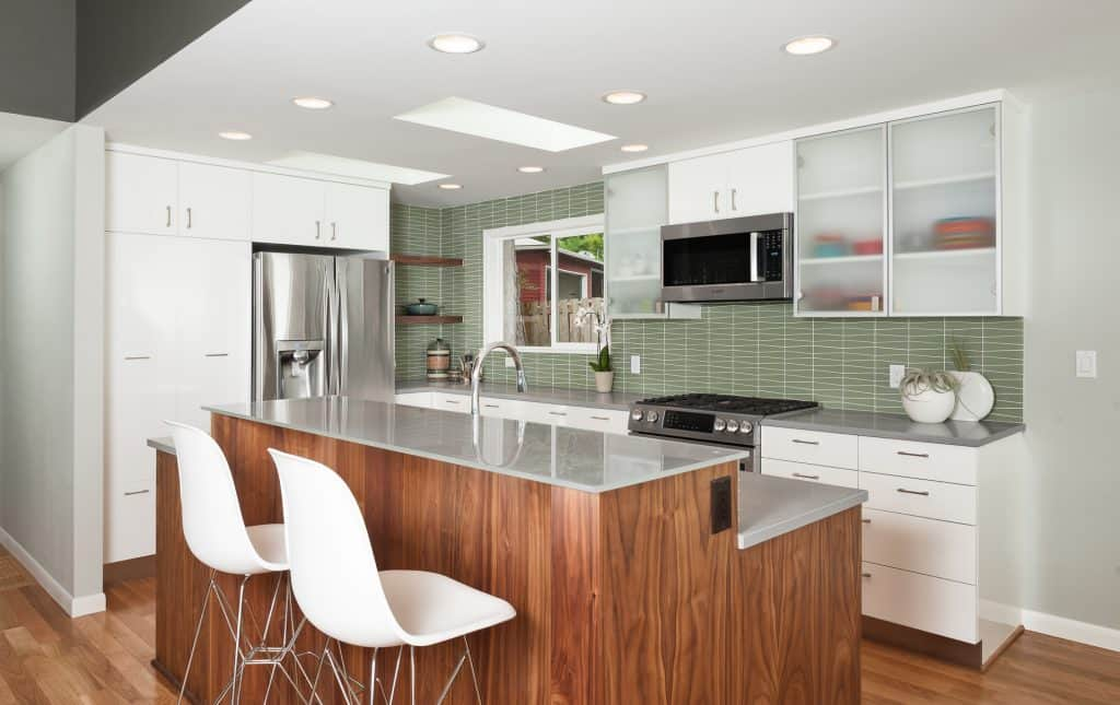 Geometric green backsplash tile in a contemporary kitchen with a wood-finished island and white cabinets and drawers.