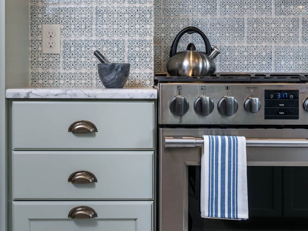 Tan and grey mosaic backsplash tile in a small modern kitchen with wooden cabinets and stainless steel appliances.