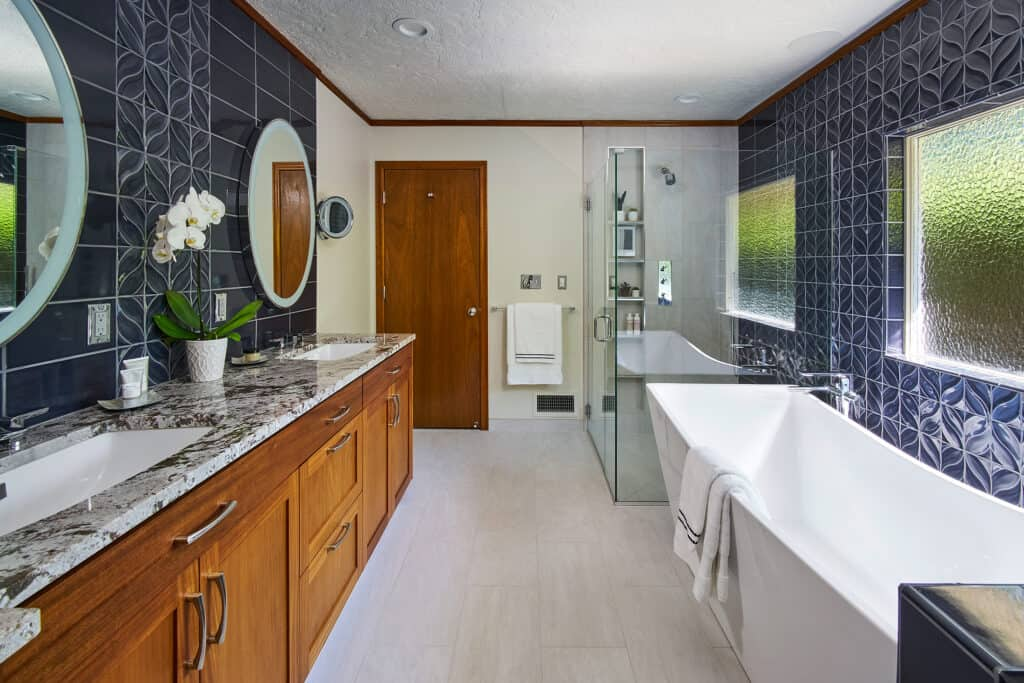 Spacious bathroom with freestanding tub and glass shower featuring blue custom tile work
