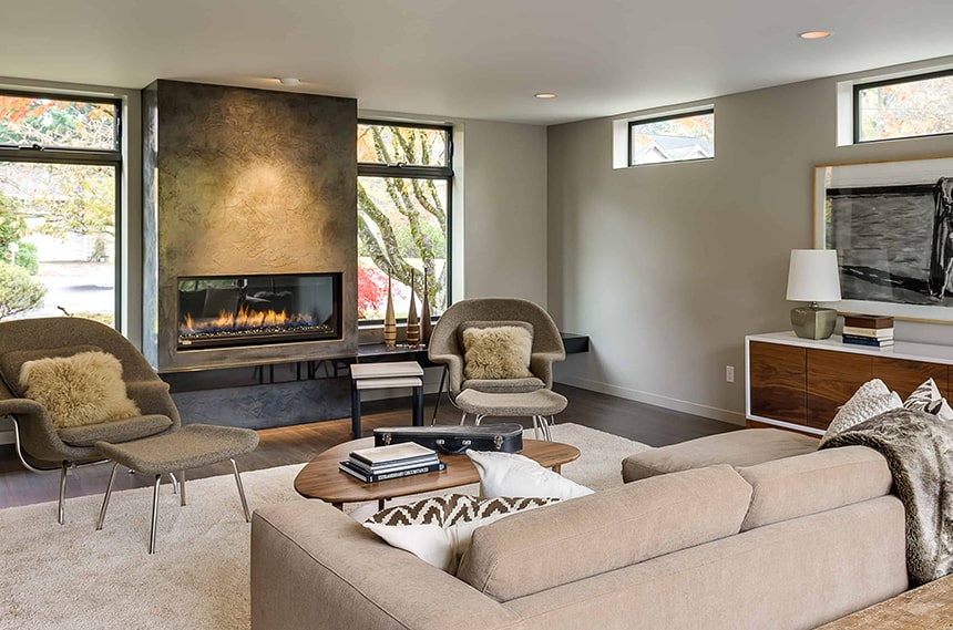 Renovated living room with large gas fireplace with beige furniture