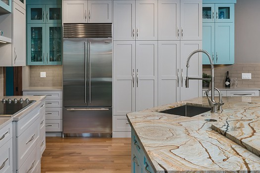 Wall of white cabinets with built-in refrigerator with bottom freezer