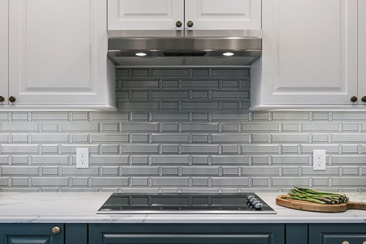Glass cooktop with vent built into cabinets with gray backsplash