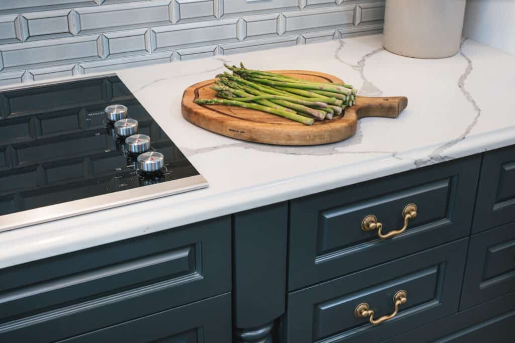 Warm colored hardware adorns dark cabinets.