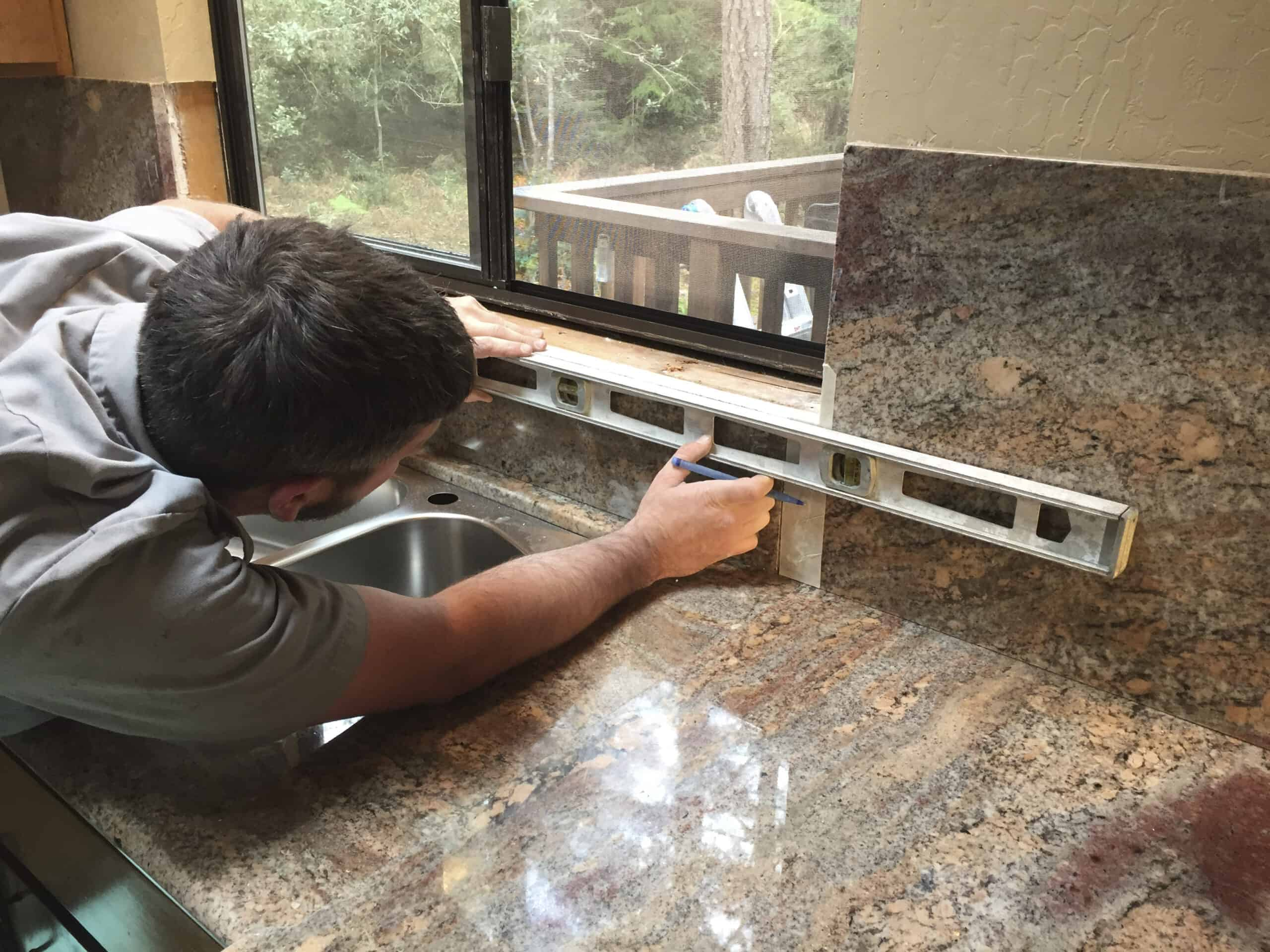 Person installing backsplash and counters