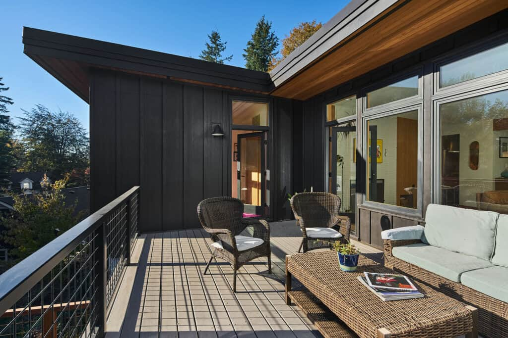 Mid Century two level home with outdoor space featuring wicker furnishings.