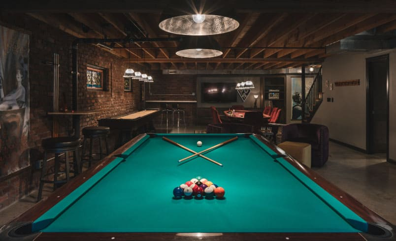 Basement man cave with pool table and exposed brick wall