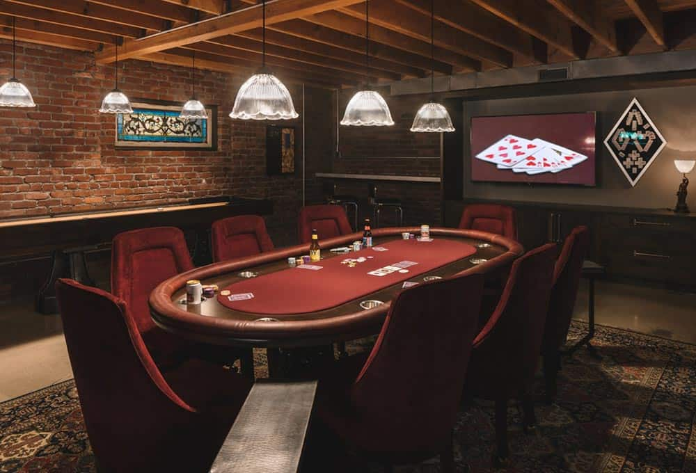 Speakeasy-style man cave with poker table and retro pendant lighting