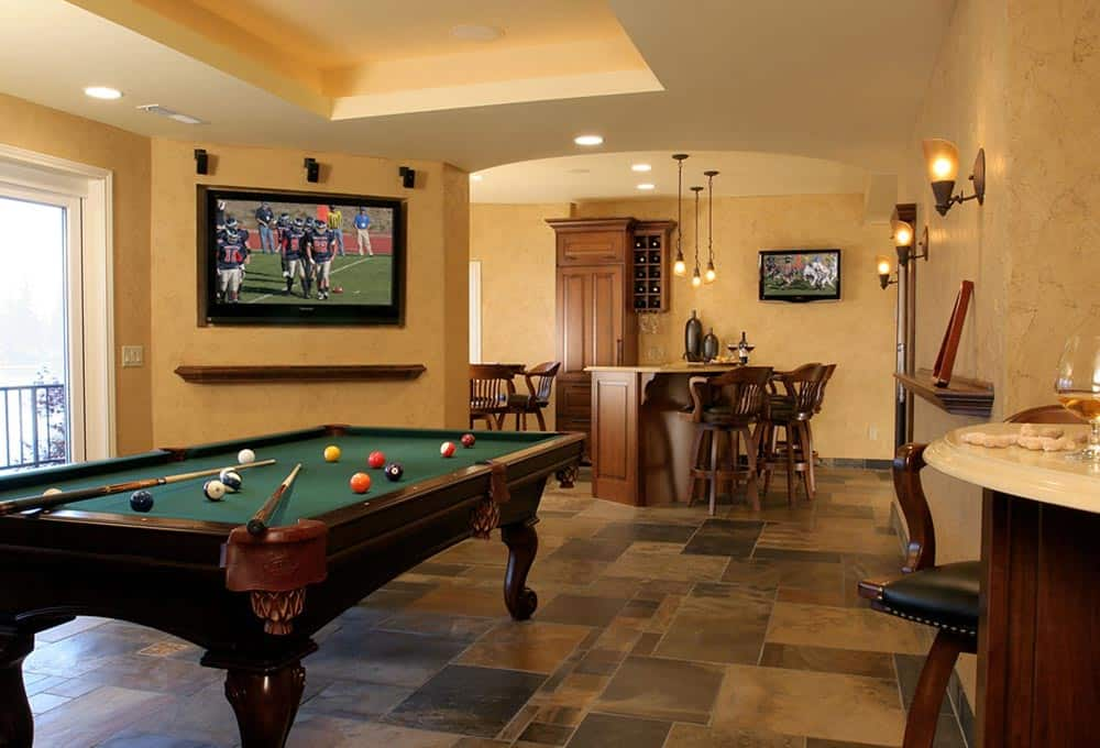 Man cave with pool table, television, and bar and natural lighting.