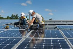 Two contractors installing solar panels on building